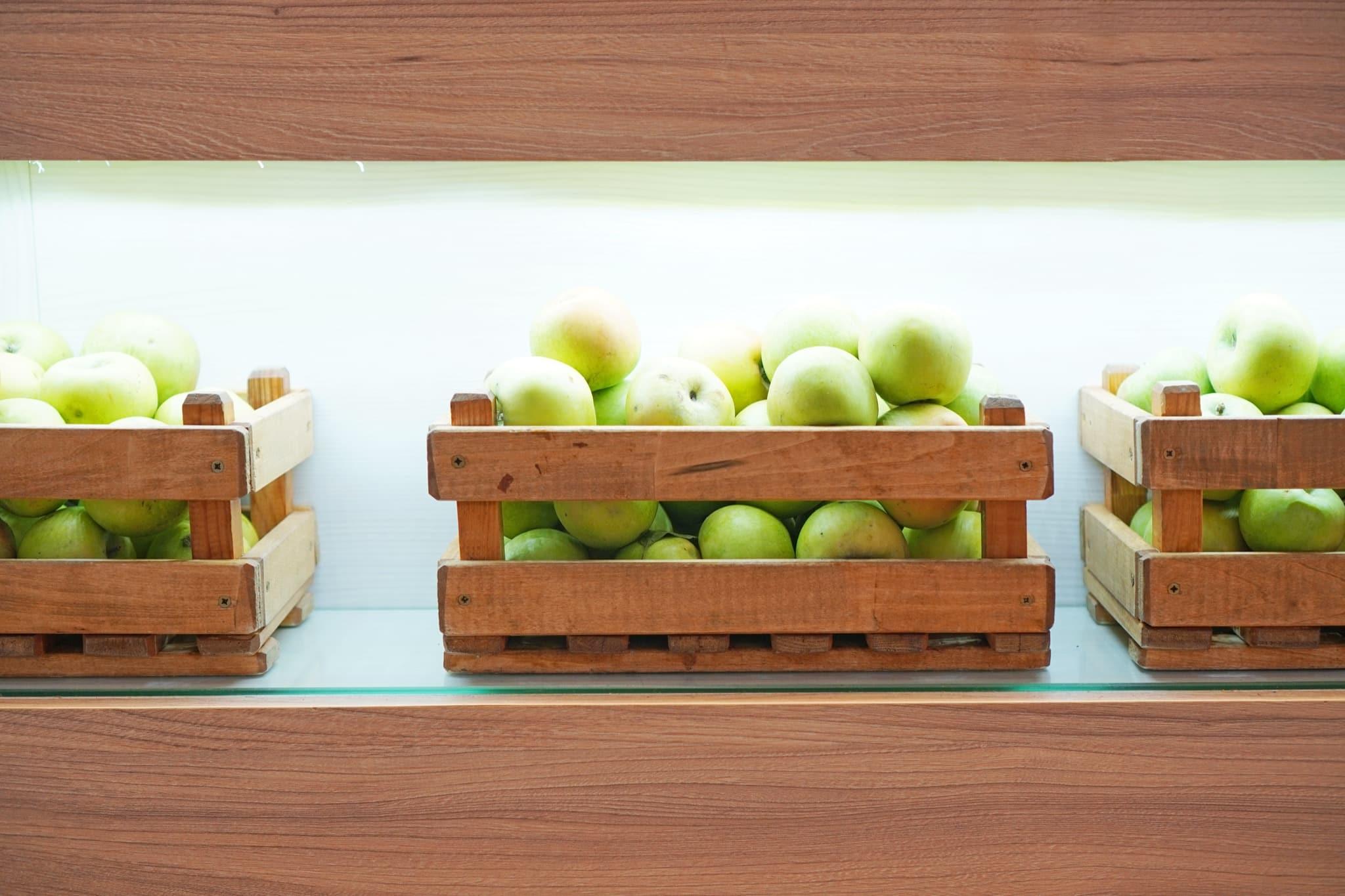 Beleuchtete Regale mit Holzkisten voller grüner Äpfel