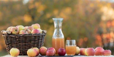 Karaffe mit frischem Obstsaft neben einem Korb voller Äpfel